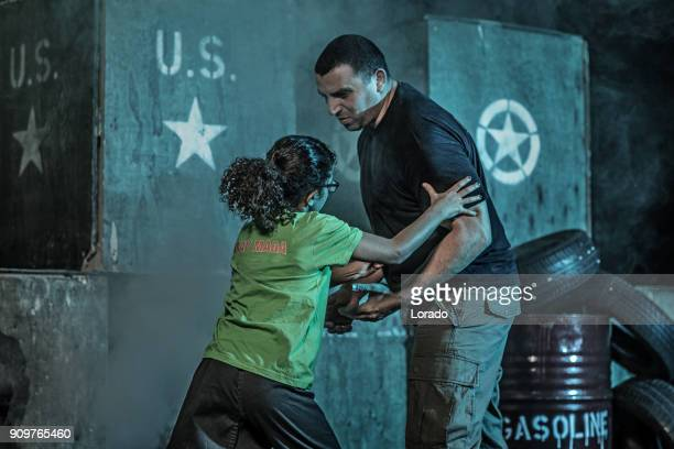 Young girl using Krav Maga fighting style against assailant in dark indoor urban setting