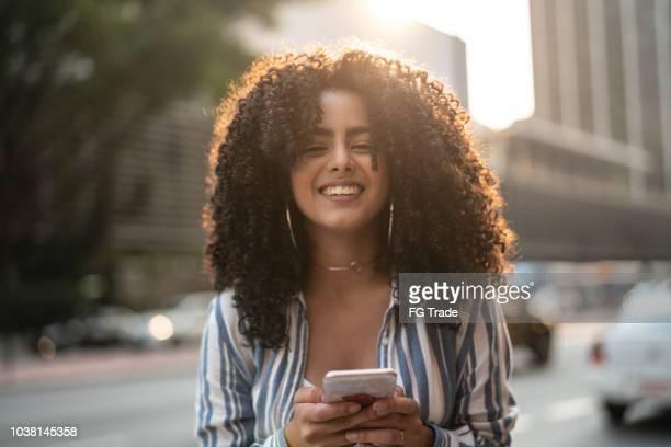 jovem garota usando mobile ao ar livre - mulheres jovens - fotografias e filmes do acervo
