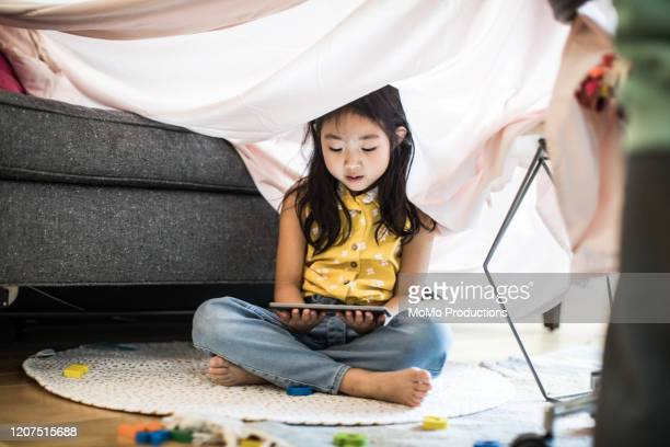 young girl using tablet in homemade fort at home - zorgeloos stockfoto's en -beelden