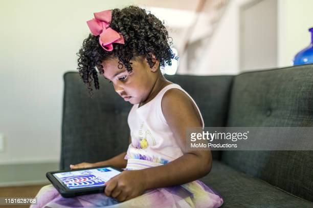 young girl (4yrs) using tablet - cartoon characters with curly hair stock photos and pictures