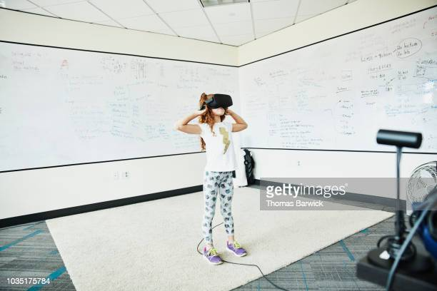 Young girl using virtual reality headset in computer lab