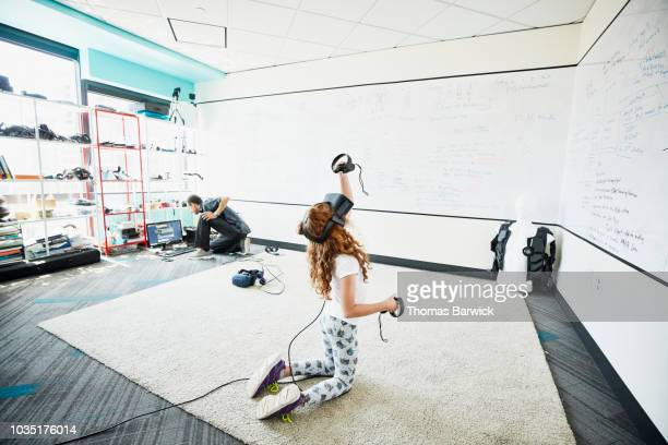 young girl using virtual reality headset in computer lab - hand on knee stock pictures, royalty-free photos & images