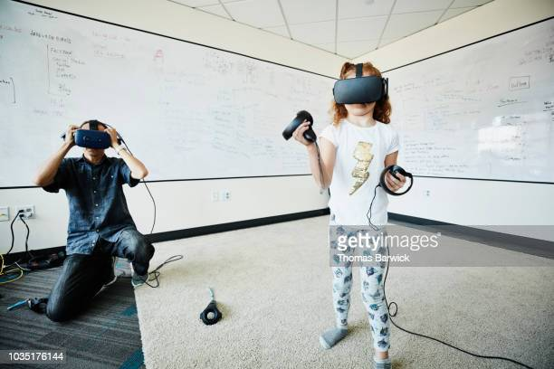 young girl using virtual reality headset to test program in computer lab - vanguardians stock pictures, royalty-free photos & images