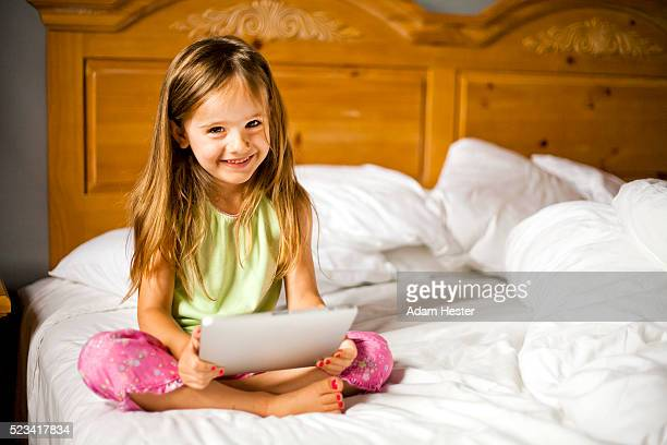 A young girl viewing a tablet device inside her home.