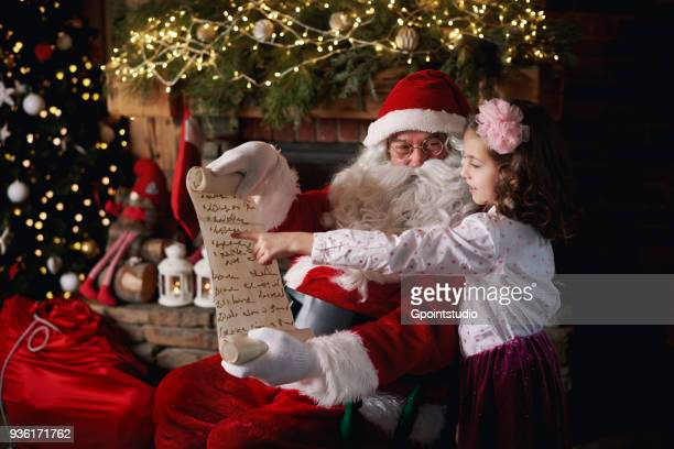 young girl visiting santa, pointing to list - santa stock photos and pictures