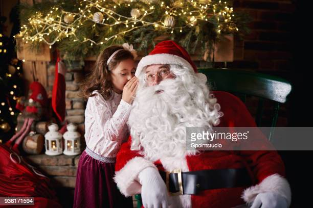 young girl visiting santa, whispering into santas ear - santa stock pictures, royalty-free photos & images