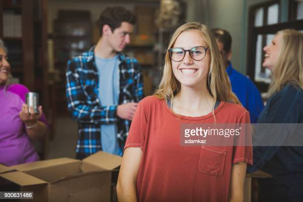young girl volunteering at food bank - charity benefit stock pictures, royalty-free photos & images