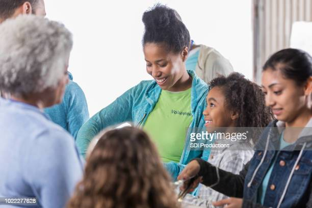 Young girl volunteers with family in soup kitchen