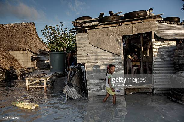 A young girl wades through the incoming sea water that flooded her house and village The people of Kiribati are under pressure to relocate due to sea...