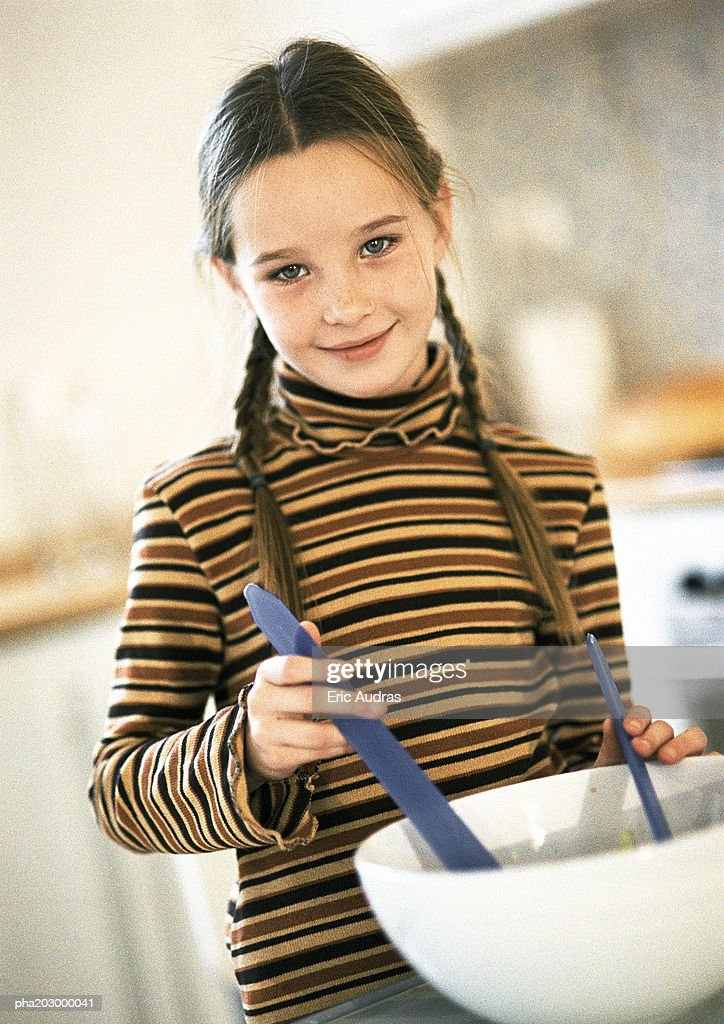 Young girl waist up, standing behind white mixing bowl, holding utensils in bowl, smiling, in kitchen setting, tilt : Stockfoto
