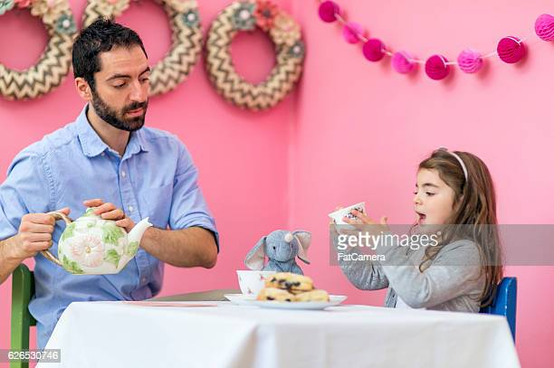Young girl waiting for dad to pour her tea