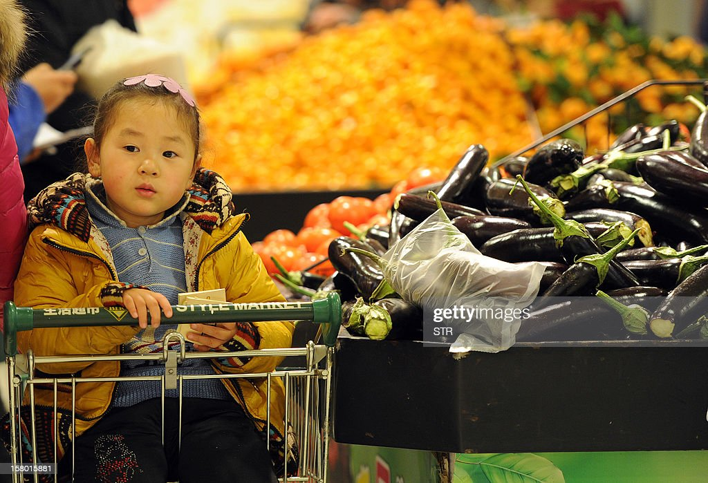 A young girl waits as her mother buys vegetables at a supermarket in Hefei, east China's Anhui province on December 9, 2012. China's inflation rate accelerated slightly to 2.0 percent in November, the National Bureau of Statistics said on December 9. CHINA