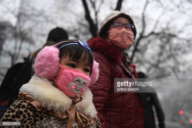 TOPSHOT A young girl waits by the road with a relative on a heavily polluted day in Shijiazhuang in northern China's Hebei province on December 21...