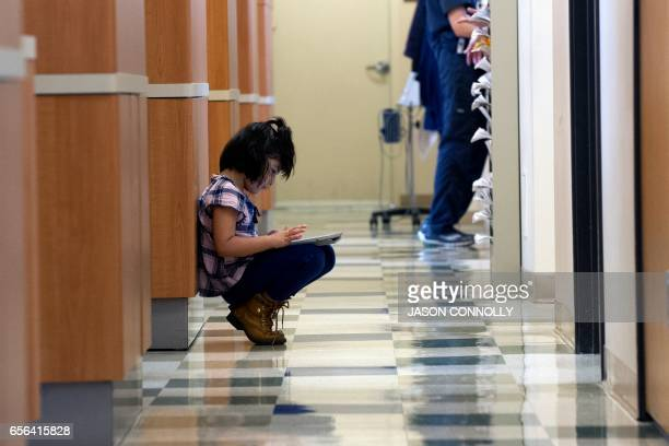 A young girl waits for a family member who is receiving dental care at Inner City Health Center in Denver Colorado on March 15 2017 Inner City Health...