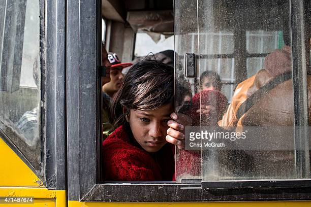 A young girl waits on board a bus to be evacuated from the city center on April 29 2015 in Kathmandu Nepal A major 78 earthquake hit Kathmandu midday...
