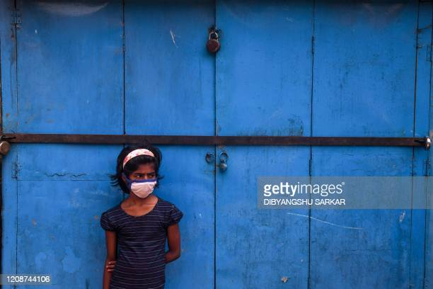 Young girl waits standing as her parents queue to collect food grains and other essential items from a shop operating under the Public Distribution...