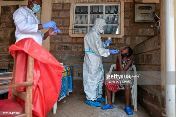 Young girl waits to be tested during a mass testing for COVID-19 coronavirus provided free of charge by the Kenyan government in the Kibera slum in...