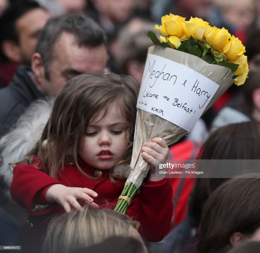 Royal visit to northern ireland pictures getty images a young girl waits to pass some flowers over to meghan markle and prince harry during izmirmasajfo