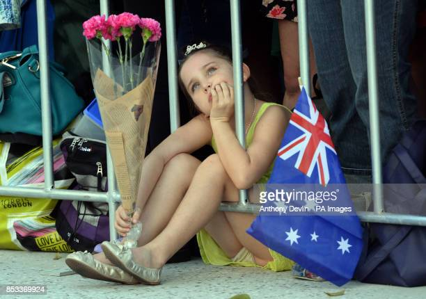 A young girl waits with flowers as the Duchess of Cambridge meets baby twins Oscar and Alyssa McCabe as the Duke and Duchess of Cambridge visit RAAF...