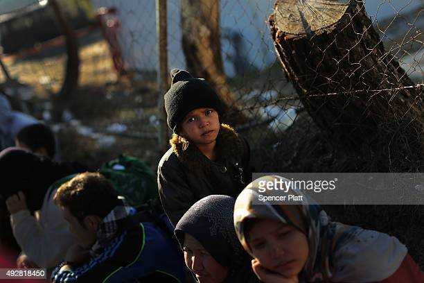 A young girl waits with her family to enter a migrant processing center after arriving from Turkey onto the island of Lesbos on October 15 2015 in...