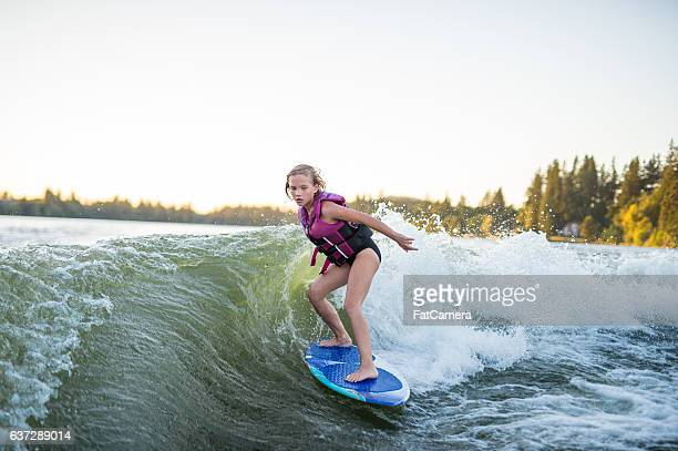young girl wakesurfing at sunset on giant wake - waterskiing stock photos and pictures