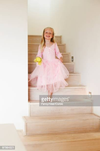 Young girl walking down a staircase