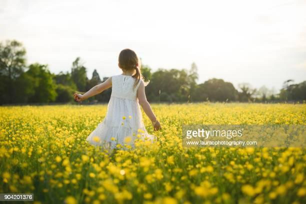 Young girl walking in buttercup field