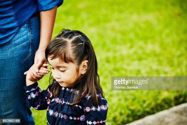 Young girl walking on sidewalk while holding mothers hand