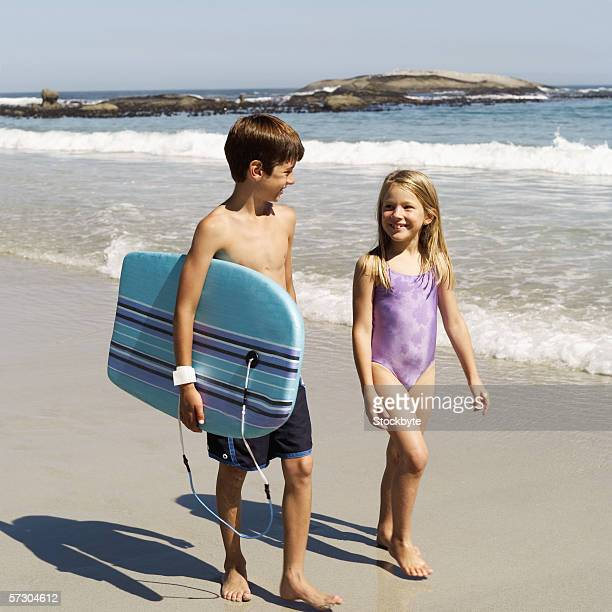 Young girl walking on the beach with a young boy (8-12) holding a surfboard