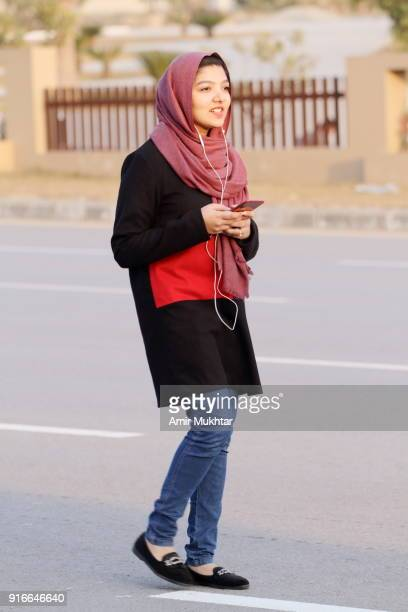 a young girl walking on the road while using cell phone - pakistan girl stock photos and pictures
