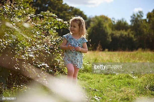 Young girl walking through field