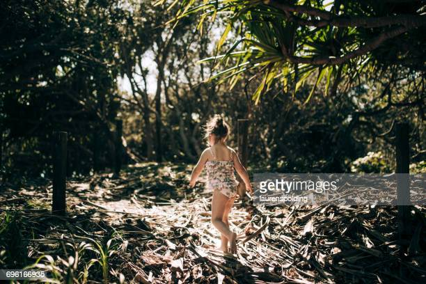 Young girl walking through sandy bush, Kingscliff, New South Wales, Australia