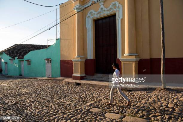 A young girl walking under beautiful sunlight in front a colonial style building at old town Trinidad, Cuba