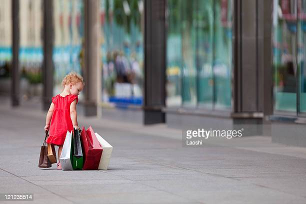 Young girl walking with a bunch of bags