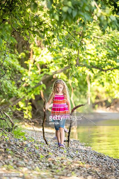 Young Girl Walking With Sticks on Riverbank