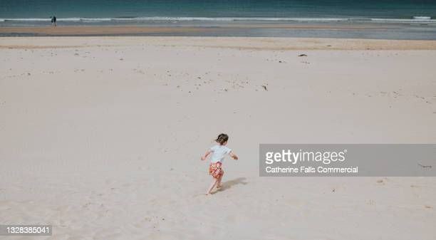 a young girl walks across a beach, dwarfed in the middle of a wide shot - distant stock pictures, royalty-free photos & images