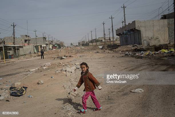 A young girl walks across a street just behind the frontline in the Entisar neighborhood on November 15 2016 in Mosul Iraq The mosul offensive has...