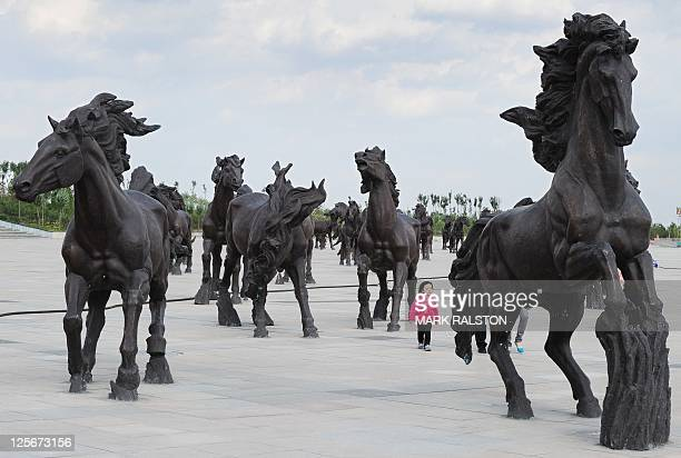 A young girl walks amongst horse statues built as a tribute to Genghis Khan whose unmarked tomb is claimed to be nearby in the city of Ordos Inner...