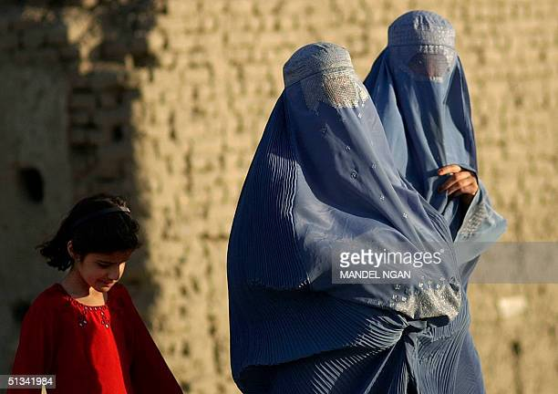 A young girl walks behind two burqaclad women late afternoon 24 May 2002 in Kabul Although the Taliban regime which made the headtoankle body...