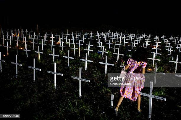 Young girl walks between crosses as she tries to find the grave of a loved one at a newly constructed mass grave for 3,000 typhoon Haiyan victims on...