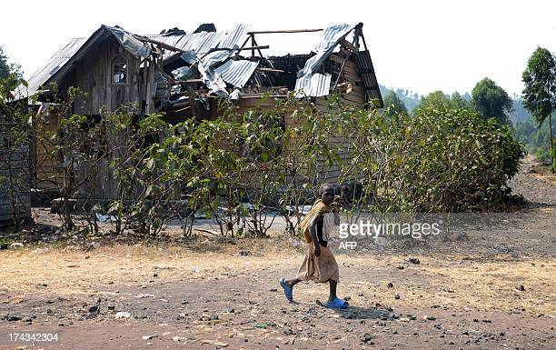 A young girl walks by a house hit by a 82 mortar of the M23 rebel group in Kanyaruchinya 15km from Goma on July 24 as rebels claimed today they had...