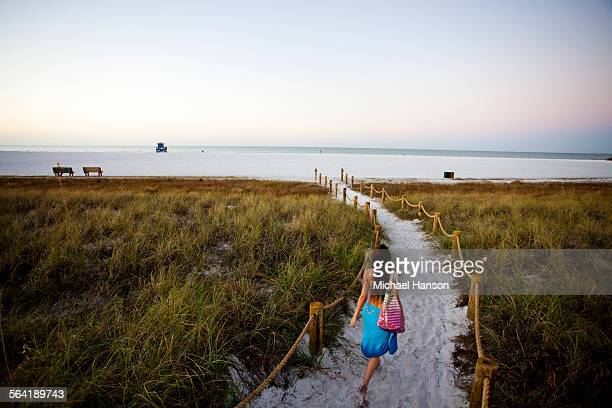 a young girl walks down a path to the beach at sunrise. - siesta key stock pictures, royalty-free photos & images