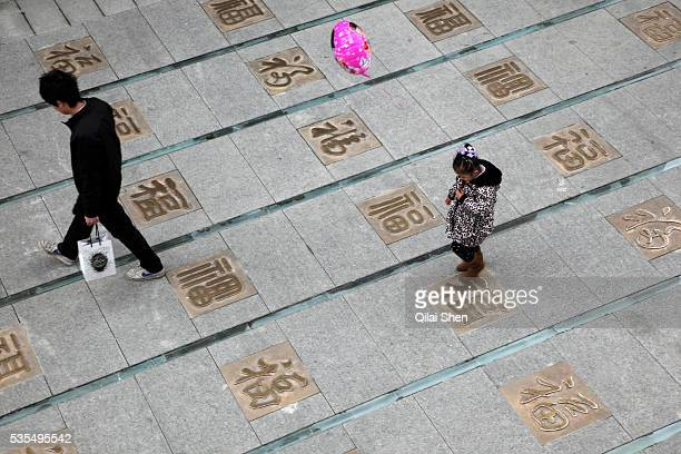 """Young girl walks over a street covered with the character """"Fu"""", which means fortune, in Jiangyin, Jiangsu Province, China on 19 February 2010."""