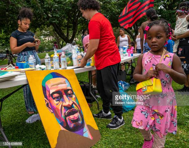 Young girl walks past a painting of George Floyd at a Juneteenth ceremony on June 19, 2021 in the Bronx borough, New York City. Juneteenth was...