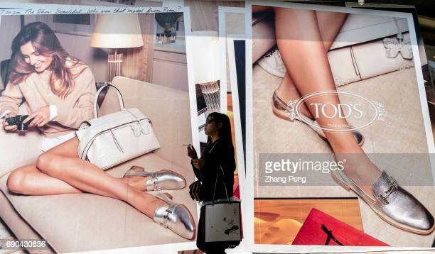 A young girl walks past the huge posters of Tod's Tod's financial data for the first quarter of 2017 shows a weak global market performance with a...