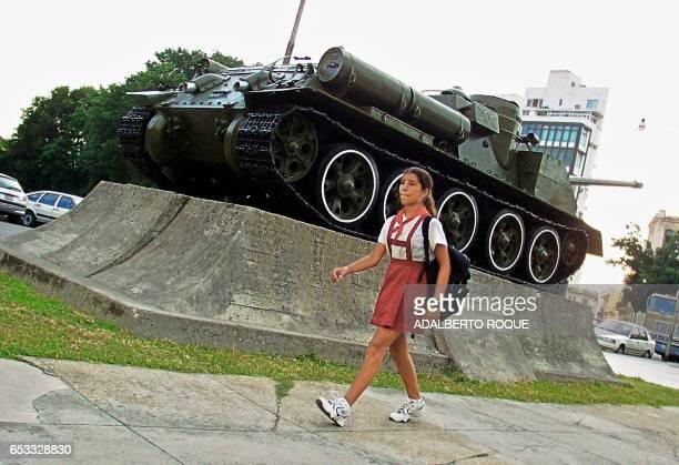 A young girl walks to school on in Cuba 03 September 2001 Una escolar pasa frente a un tanque de guerra expuesto en un museo local el 03 de setiembre...
