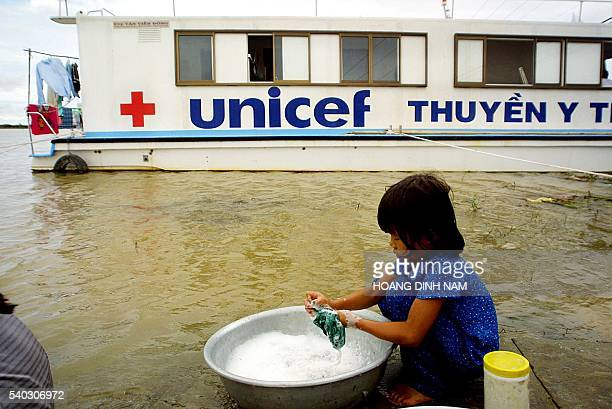 A young girl washes clothes near a UNICEFfunded medical boat anchored at the flooded district of Tam Nong in Southern Mekong delta province of Dong...