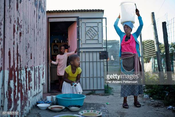 A young girl washes dishes outside the family house while the grandmother is carrying a bucket to fetch drinking water in Guguletu a township about...