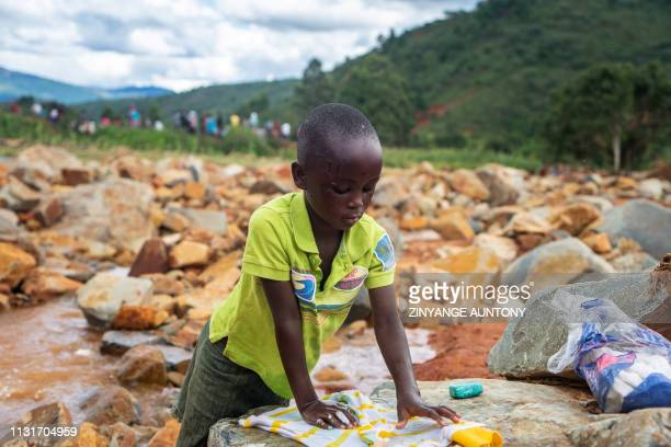 A young girl washes in a stream her donated dress near the Chimanimani Rural Hospital where displaced people following cyclone Idai are sheltered in...