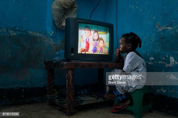 A young girl watches American cartoons in a room inside the ruins of the former US embassy in Mogadishu from the nineteen eighties This building and...